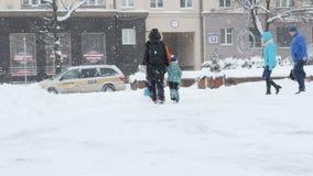 Glückliche Familie, die zusammen an der schneebedeckten Stadtstraße während der Winterurlaube geht stock footage