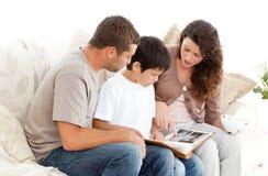Glückliche Familie, die zusammen ein Fotoalbum betrachtet Lizenzfreies Stockfoto