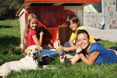 Glückliche Familie, die zusammen eine Hundehütte errichtet Stockbild
