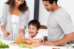Glückliche Familie, die zusammen einen Salat zubereitet stockfotos
