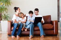 Glückliche Familie, die zusammen mit einem Laptop spielt Stockfotos