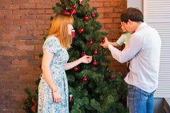 Glückliche Familie, die zusammen Weihnachtsbaum verziert Vater, Mutter und Sohn Nettes Kind zicklein Lizenzfreies Stockbild