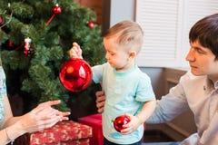 Glückliche Familie, die zusammen Weihnachtsbaum verziert Vater, Mutter und Sohn Nettes Kind zicklein stockfoto
