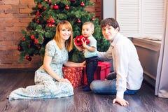 Glückliche Familie, die zusammen Weihnachtsbaum verziert Vater, Mutter und Sohn Nettes Kind zicklein Stockfotografie