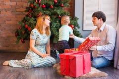 Glückliche Familie, die zusammen Weihnachtsbaum verziert Vater, Mutter und Sohn Nettes Kind zicklein Stockbild
