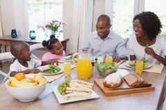 Glückliche Familie, die zusammen zu Mittag isst Lizenzfreie Stockfotos