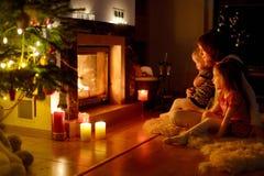 Glückliche Familie durch einen Kamin auf Weihnachten Lizenzfreies Stockbild