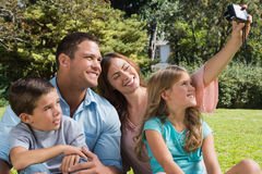 Glückliche Familie in einem Park, der Fotos macht Stockfotos
