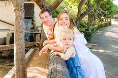 Glückliche Familie - Eltern mit dem Kleinkindmädchenkind, das Spaß im Zoo hat Familienerholung, Konzept der Zeit zusammen aufwend stockfotografie
