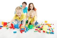 Glückliche Familie. Eltern mit zwei Kindern, die Spielwarenblöcke spielen Stockfotos