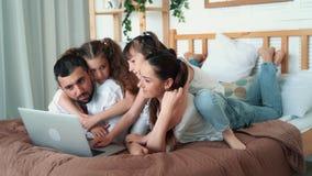 Glückliche Familie, Eltern und zwei Töchter, die Karikatur auf Laptop, Zeitlupe aufpassen stock footage
