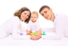 Glückliche Familie erzieht zusammen und das Baby, das mit Spielwaren spielt Stockfotos