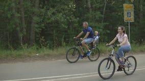 Glückliche Familie fährt auf Fahrräder im Wald stock video footage