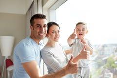 Glückliche Familie am Fenster lizenzfreie stockfotografie