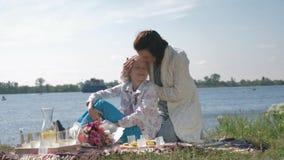Glückliche Familie, fröhliches Mutterzopfhaarkindermädchen und während des Entspannung auf Picknick auf Rasen in Verbindung stehe stock video