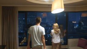 Glückliche Familie, Frau, Mann auf dem Hintergrund von Wolkenkratzern im panoramischen Fenster am Abend lizenzfreie stockfotografie