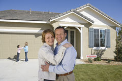 Glückliche Familie in Front Of New House Lizenzfreie Stockbilder