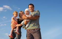 Glückliche Familie gegen den Himmel Lizenzfreie Stockfotografie