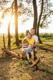 Glückliche Familie, gehend in die Frischluft, die Eltern, die auf einem Klotz mit seinem Kind sitzen lizenzfreie stockbilder