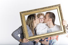 Glückliche Familie gestaltet durch einen Bilderrahmen stockfoto