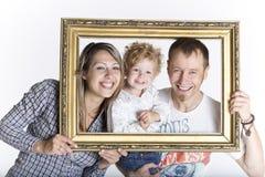 Glückliche Familie gestaltet durch einen Bilderrahmen stockfotografie