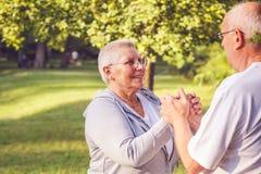 Glückliche Familie - Hände von älteren Paaren während des Wegs im Park auf Sonne Lizenzfreies Stockbild