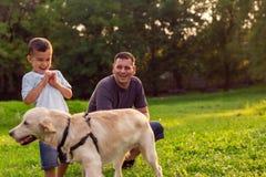 Glückliche Familie hat Spaß mit golden retriever - Vater und hallo lizenzfreie stockfotografie