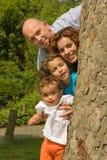Glückliche Familie hinter einem Baum lizenzfreie stockfotos