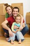 Glückliche Familie in ihrem neuen Haus mit Lots Kästen Lizenzfreies Stockbild