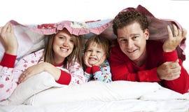 Glückliche Familie im Bett Stockfotografie