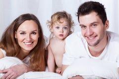Glückliche Familie im Bett Stockbild