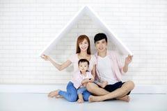 Glückliche Familie im neuen Haus mit Dach lizenzfreie stockfotos