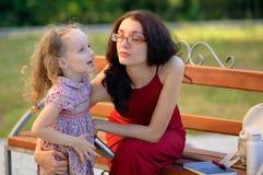 Glückliche Familie im Stadt-Park während Sunny Warm Weathers Äußeres Porträt der jungen Mutter und ihrer netten kleinen Tochter stockbilder