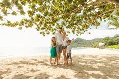 glückliche Familie im Urlaub, die auf Strand umfasst lizenzfreies stockbild