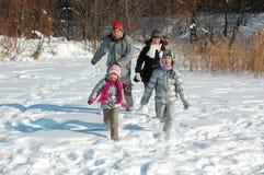 Glückliche Familie im Winter, Spaß habend und draußen spielen mit Schnee am Feiertagswochenende lizenzfreie stockfotografie