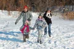 Glückliche Familie im Winter, Spaß mit Schnee habend draußen lizenzfreie stockbilder