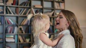 Glückliche Familie - junges Paar, das jüngere Babytochter, nachdem dem Spielen mit Farben küsst stock video footage