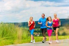 Glückliche Familie läuft draußen in Sommer stockfotografie