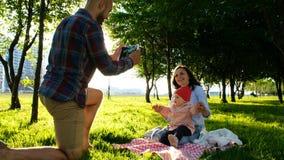 Glückliche Familie legt auf das plädierte und Handelnselfie mit einem Baby bei Sonnenuntergang im Park Vater macht Fotos von Lizenzfreie Stockfotos