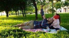 Glückliche Familie legt auf das Plaid und tut selfie mit einem Baby bei Sonnenuntergang im Park Eltern macht Fotos von Stockbild