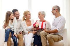 Glückliche Familie mit Bündel und Geschenkbox zu Hause Lizenzfreies Stockfoto