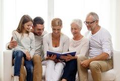 Glückliche Familie mit Buch- oder Fotoalbum zu Hause Stockfotografie