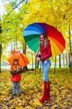 Glückliche Familie mit bunten Regenschirmen im Herbstpark Stockfotografie