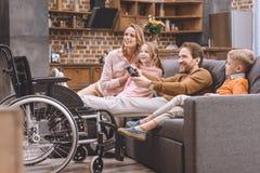 glückliche Familie mit dem behinderten Vater, der mit Steuerknüppel spielt lizenzfreie stockbilder