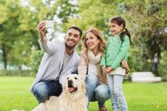 Glückliche Familie mit dem Hund, der selfie durch Smartphone nimmt lizenzfreies stockbild