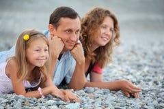 Glückliche Familie mit dem kleinen Mädchen, das auf steinigem Strand liegt stockbild