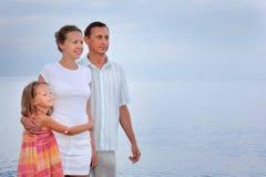 Glückliche Familie mit dem Mädchen, das auf dem Strand, glättend steht Stockbild