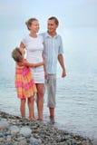 Glückliche Familie mit dem Mädchen, das auf dem Strand, glättend steht Stockfotografie