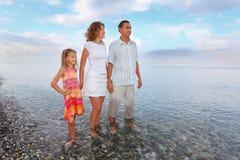 Glückliche Familie mit dem Mädchen, das im Meer Knie-tief steht Lizenzfreie Stockfotos
