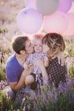 Glückliche Familie mit den bunten Ballonen, die auf einem Lavendelgebiet aufwerfen lizenzfreie stockfotografie